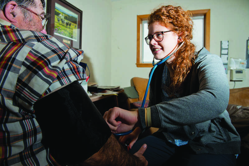 Senior Elora Blomberg takes the blood pressure of a worker at one of the several farms she visited as part of the nursing student group last fall.