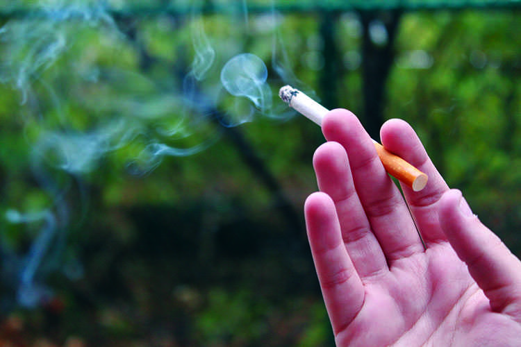 A UWEC student stops to smoke in a designated area and poses before heading to their next class. Photo Illustration.