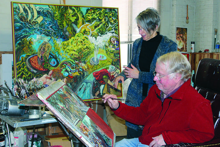 Barbara Shafer looks over husband Andy Shafer's shoulder as he works on a new painting. © 2014 Katie Bast.