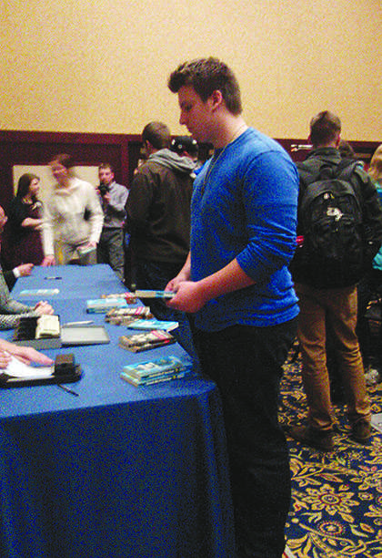 Senior Dane Jaskowiak purchases Catch Me If You Can, a book about Frank Abagnale's life, at the reception after Wednesday's forum. Jaskowiak said he wanted to hear Abagnale's perspective on the movie about his life. © 2014 Elizabeth Jackson.