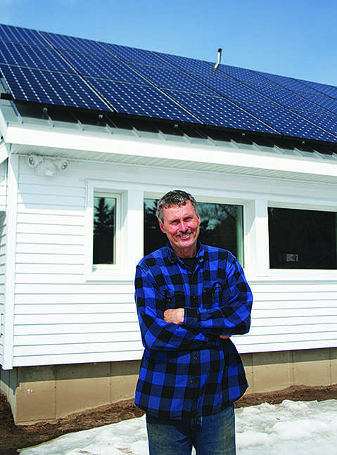 SUN SAVINGS: Jim Dickerson built this solar panel array last summer. He's now running his house on clean energy alone. © 2014 Nate Beck