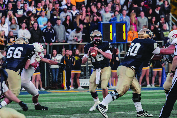 Senior quarterback Mark Munger looks for a pass downfield against St. Johns Saturday night at Carson Park.