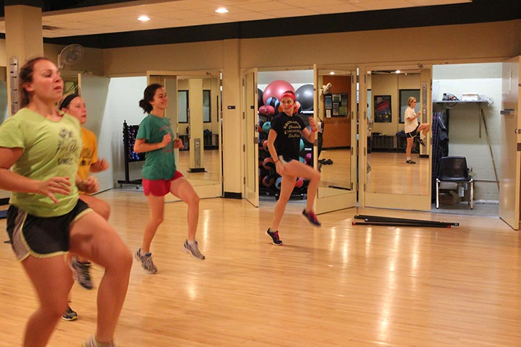 Senior kinesiology major, Karli Jacobus, far right, leads a warm-up exercise at a Strength & Tone group exercise class, which started 6 a.m. Wednesday in McPhee Physical Education Center. Jacobus is one of 18 students who lead free group exercises.