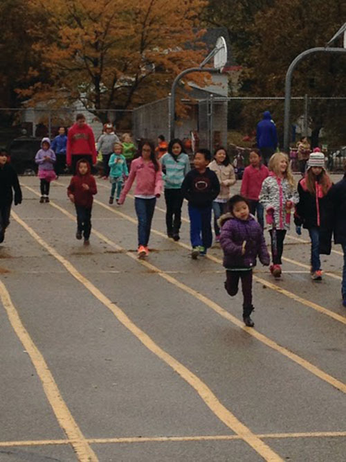 Students run and walk the lap's final straightaway.