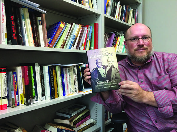 UW-Eau Claire professor of English and history Joe Orser poses with his recently published book, The Lives of Chang and Eng: Siams Twins in Nineteenth Century America. The text, published by the University of North Carolina Press, will be celebrated by the university community at a book signing event at 6 p.m. Monday in the Menominee Room of Davies Center. - Photo by Courtney Kueppers