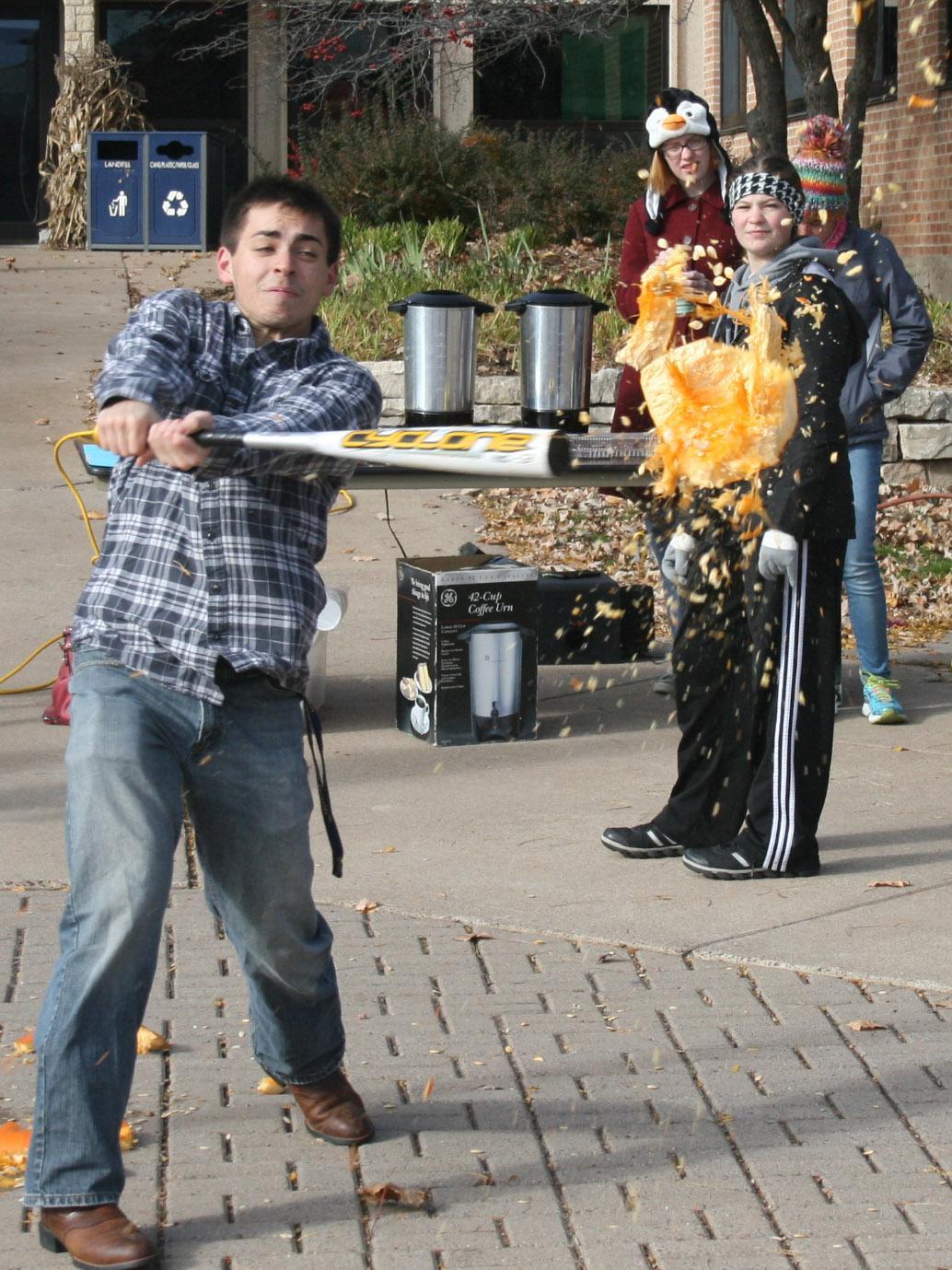 Fellow students watch as freshman chemistry major Chris Hartwick takes his turn at pumpkin smashing. - Photo by Austin Mai