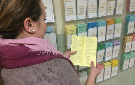 Ashley Galoff, the Master's Level intern at Counseling Services at UW-Eau Claire, explains a pamphlet discussing the signs of test anxiety. Counseling for test anxiety is among the services provided by the free center located in Old Library, making it a viable option for low-income students.