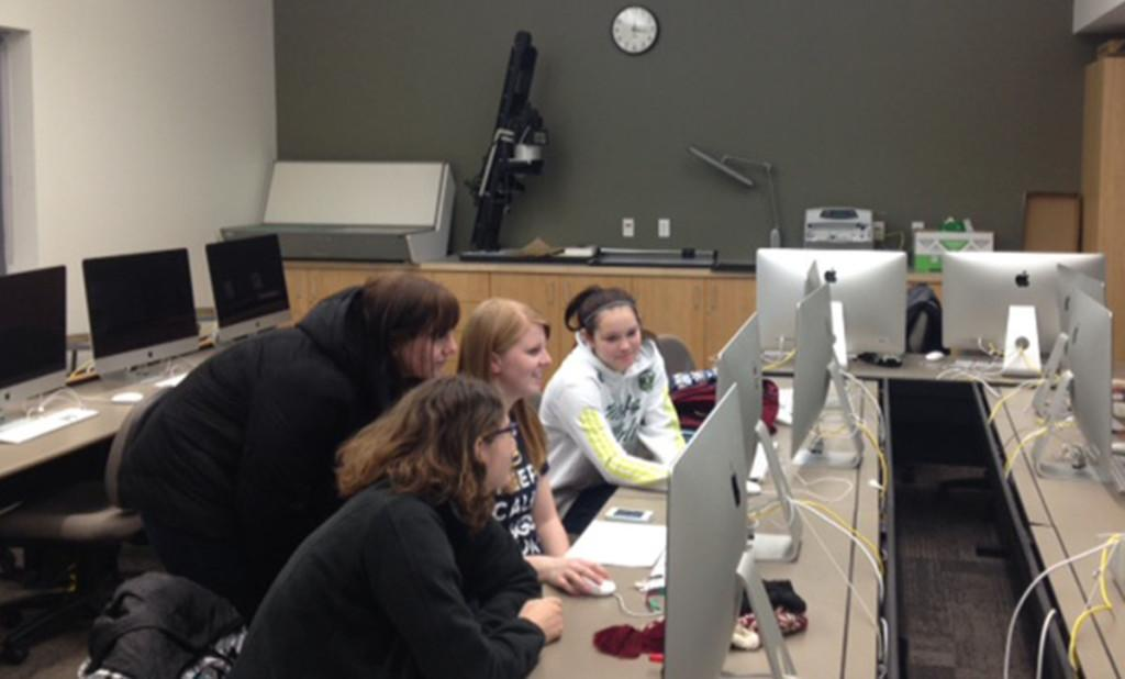 Students gather around a Mac computer in the CJ department's Mac lab earlier this week.