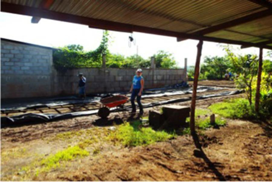 UW-Eau Claire senior Michaela Schopf transports adobe mix to the brick-making station in El Pantanal, a community in Granada, Nicaragua last fall.