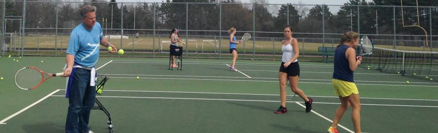 Men's and women's tennis head coach Tom Gillman practices drills with the women's team at practice.
