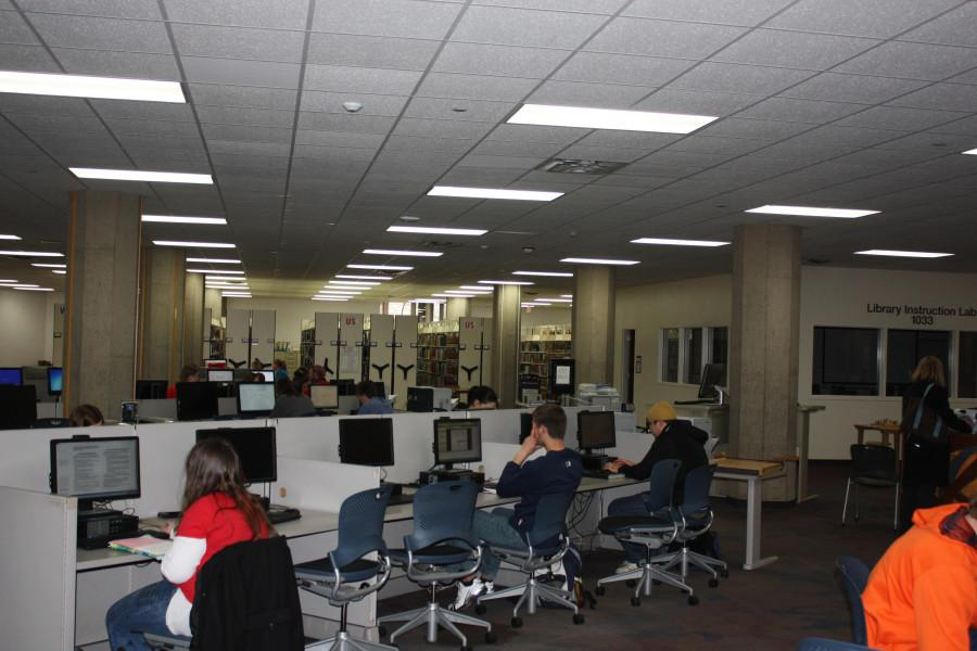 At the McIntyre library, students sit at the computers and text on their phones.