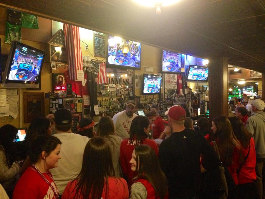 Badger fans cheer and watch the Wisconsin men's basketball team during the national championship game at Dooley's Pub.