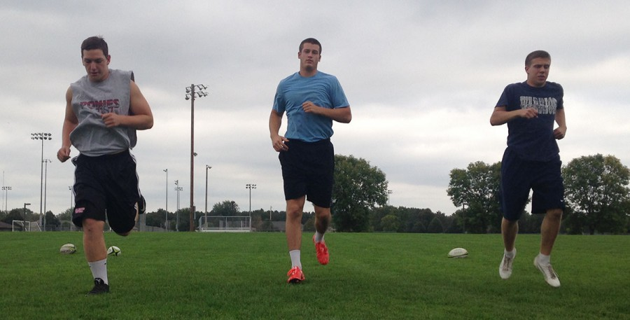 UW-Eau Claire Men's Rugby Club members Ryan Floen, Joe Zimmer and Riley Wingate warm up with some drills at Bollinger Fields before practice on Sept. 22.