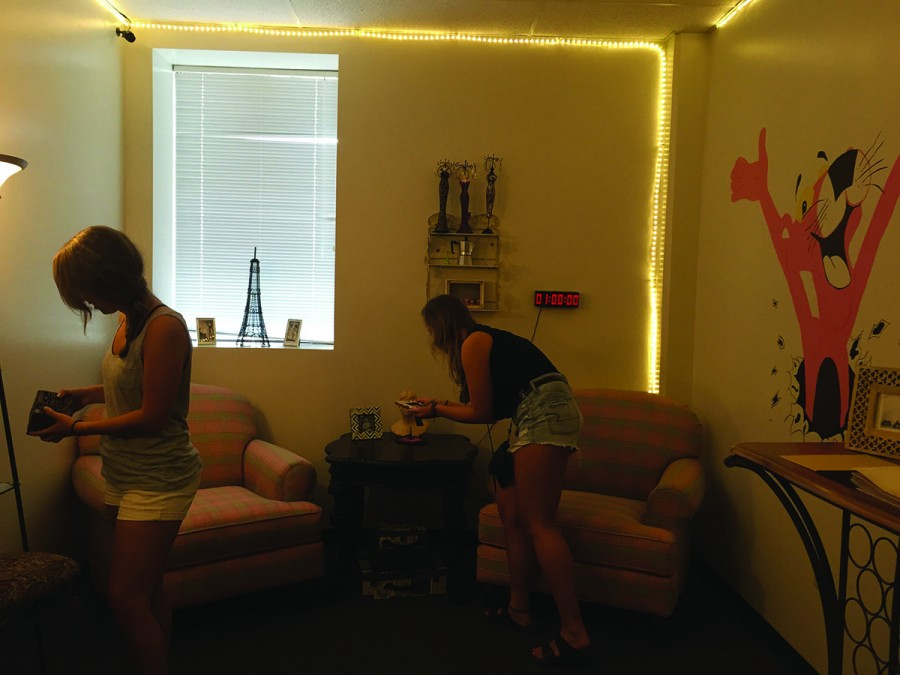 Eau Claire students Kelsey Rolefson and Emily Johnson hunt for clues to escape the Pink Panther in Paris room at Tactical Escape 101.