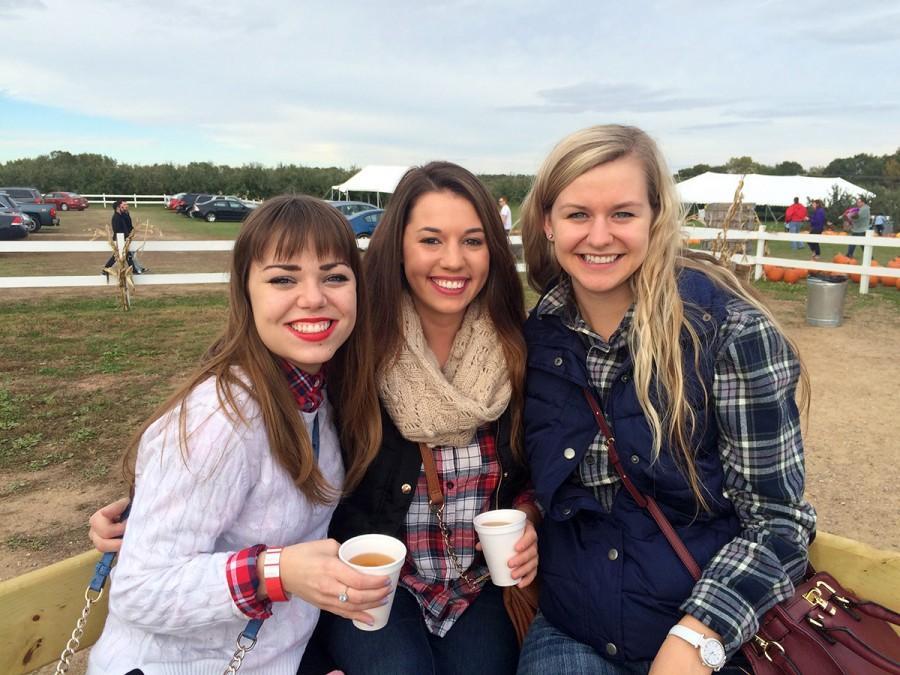 Sami West, Hailey Novak and Sam Pitts enjoy apple cider on the hayride at Ferguson's Apple Orchard.