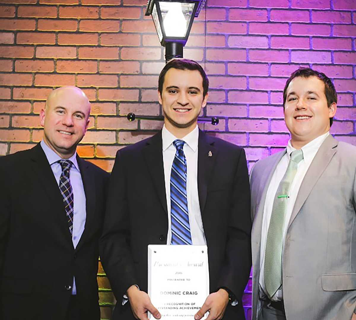 Dominic Craig receives the Rookie Entrepreneur award from the president of CollegePro Dave Rychley (left) with his coach Trevor Hicks (right)