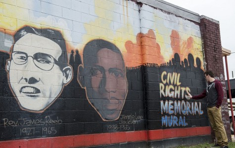 A student poses with a mural found on the Civil Rights Pilgrimage.