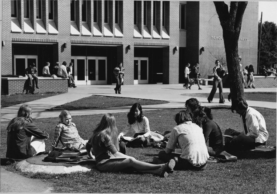 A group of students sit in a circle while studying outside Schneider Social Science Hall in 1976.