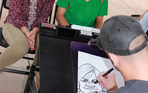 SAY CHEESE: Students Monica Gross and Cody Stankowski pose for their caricature drawing at the fourth annual UW meets EC in Phoenix Park Friday.