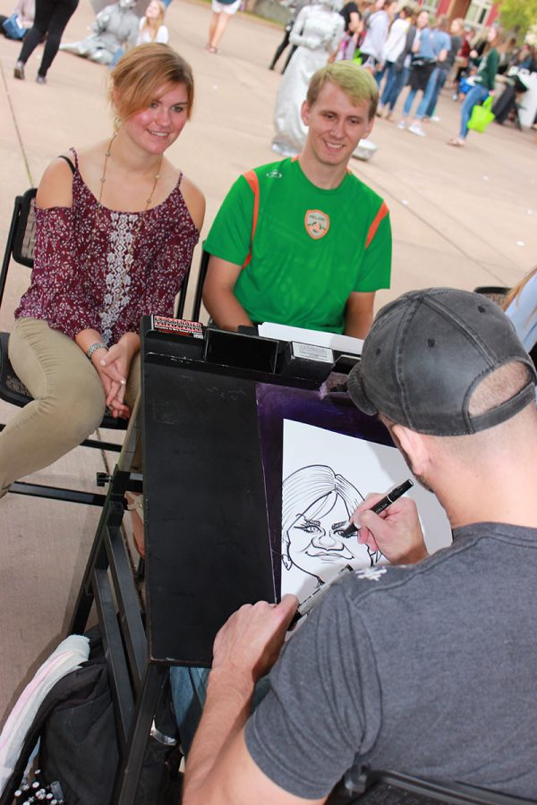 SAY+CHEESE%3A+Students+Monica+Gross+and+Cody+Stankowski+pose+for+their+caricature+drawing+at+the+fourth+annual+UW+meets+EC+in+Phoenix+Park+Friday.