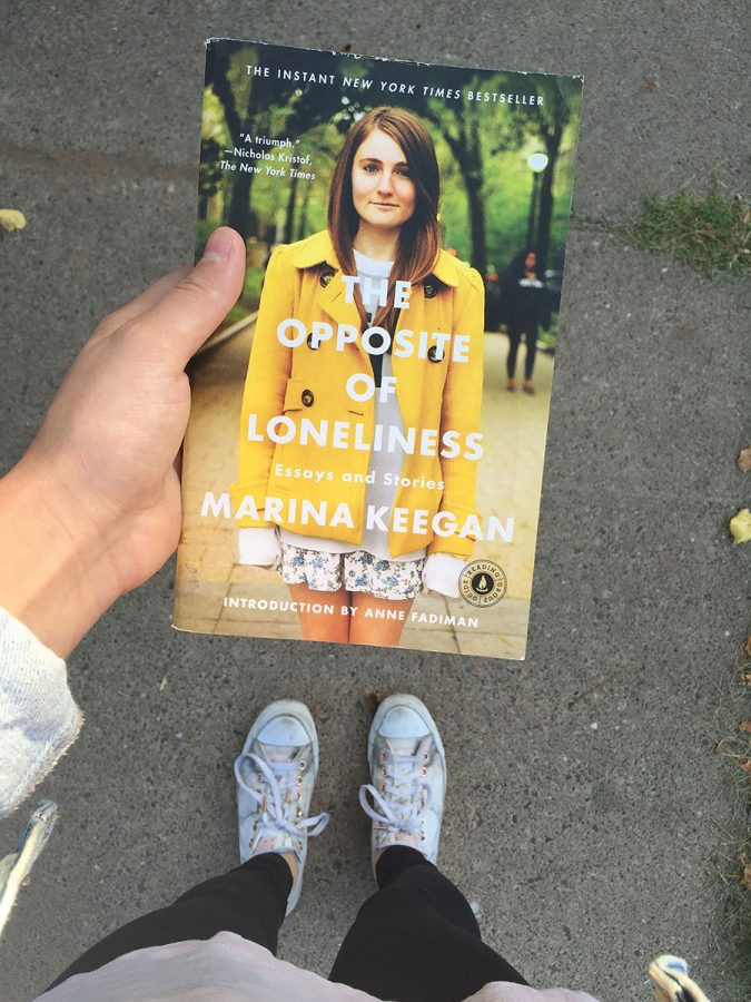 """Novak stands on the sidewalk with Marina Keegan's book, """"The Opposite of Loneliness"""" in hand. The book made her realize that happiness is more than a checklist."""