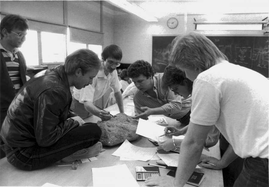 In a 1990s geology class, students studied the characteristics of a large rock with Professor Kent Syverson.