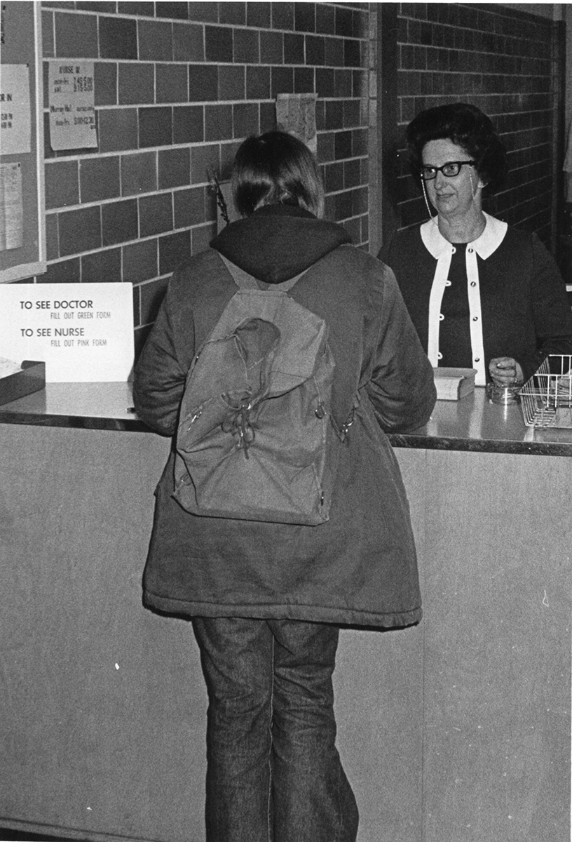A student stands at the reception desk of the campus health center, circa 1960s.