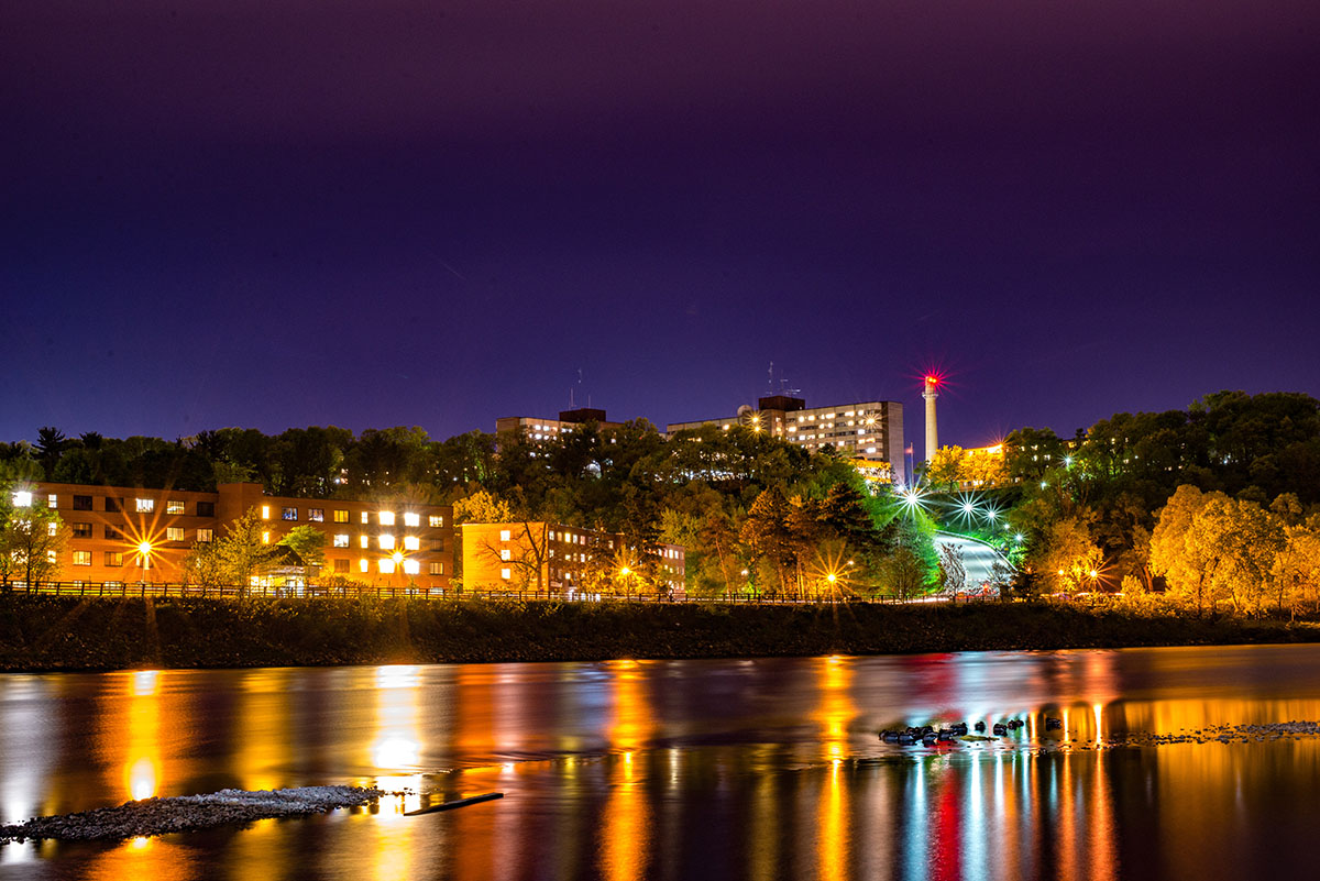 After nightfall, setting up a picturesque shot of the lower campus aglow from the opposing bank.
