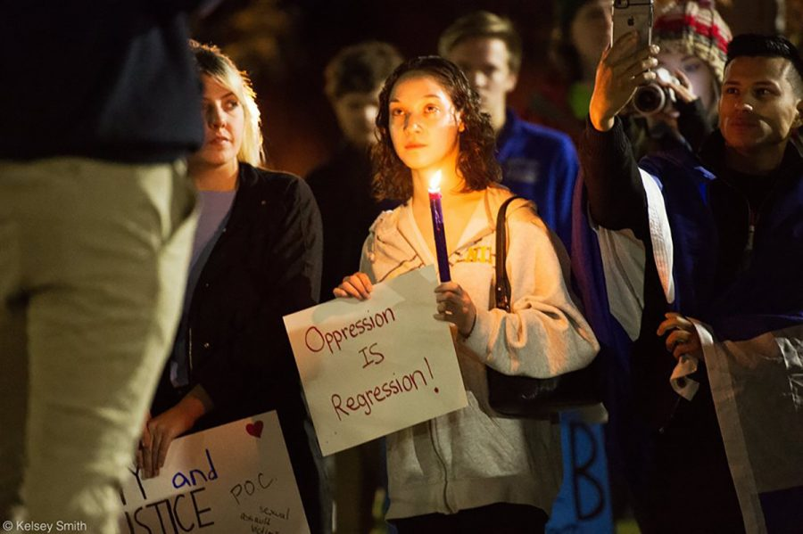 Senior social work student Diosa Marie Withington listens to speeches before the peaceful protest Thursday evening. Withington participated in both events and said they served different purposes.