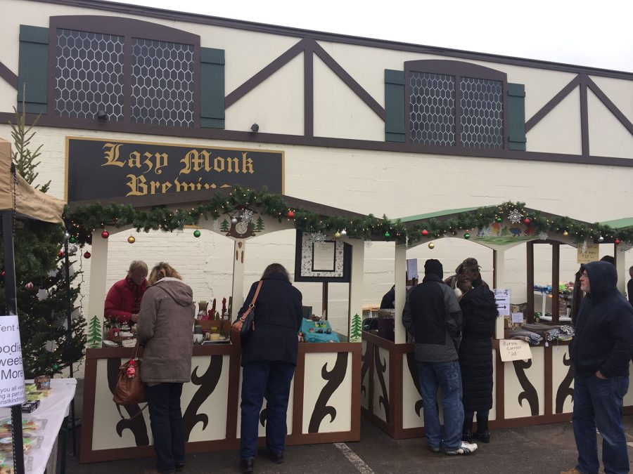 Eau Claire community members check out homemade lip balm and soaps at Stephanie Schneider's stand at Christkindlmarkt last Saturday outside Lazy Monk Brewing.