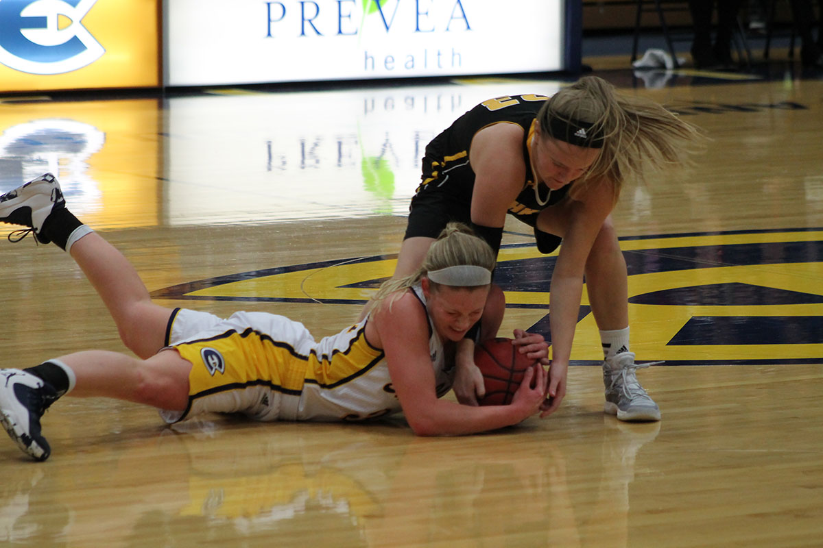 Eau Claire's Arien Brennan and Oshkosh's Morgan Kokta struggle over possession of the ball.