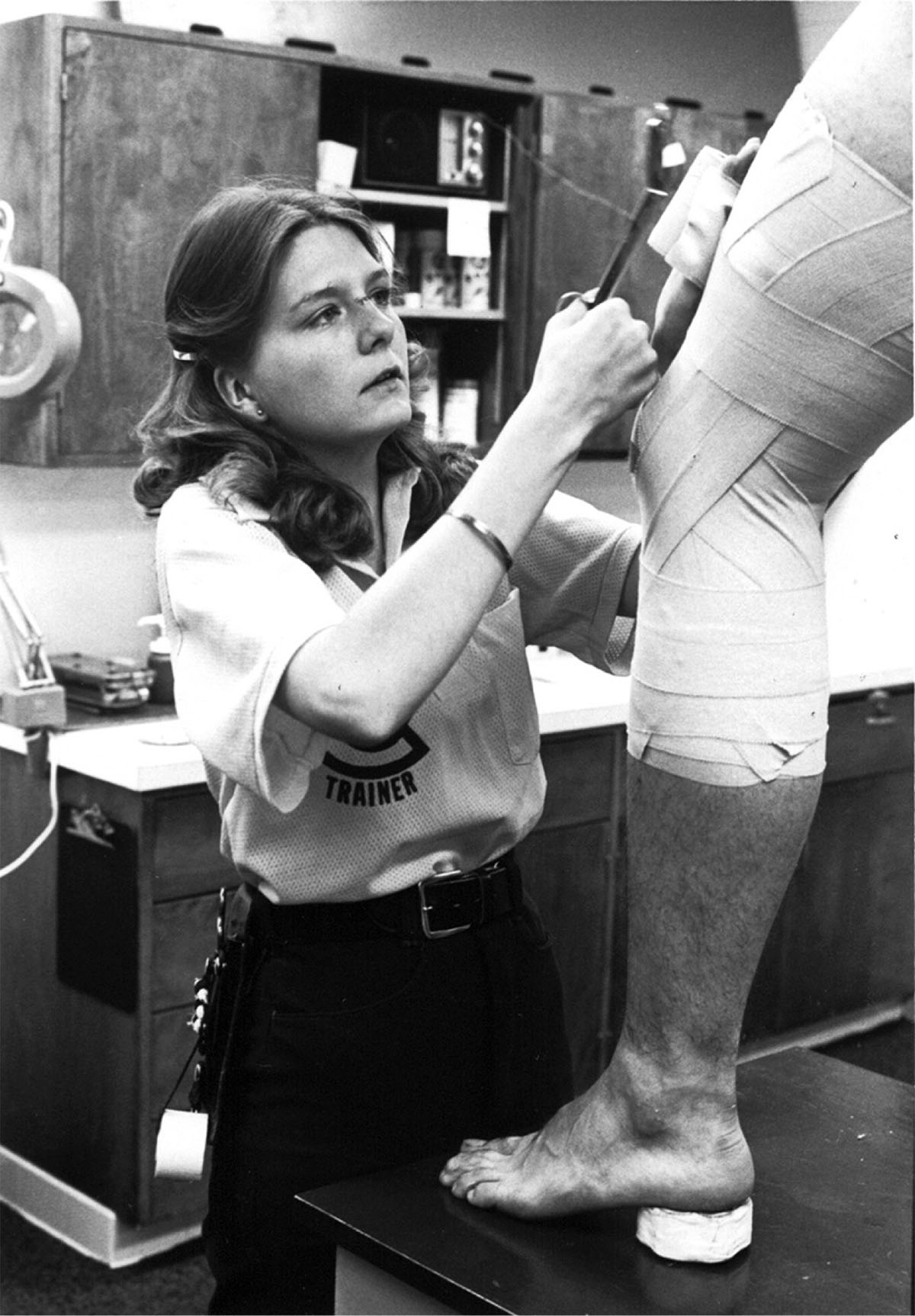 Pictured is athletic trainer, Barb Jenneman taping a football player's leg in 1979. Barb was trainer for the men's football team, an example of a possible career for a Kinesiology student.