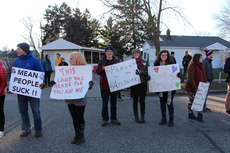 Student's hold up signs supporting immigration at Trump's pre-election visit to Eau Claire in 2016.