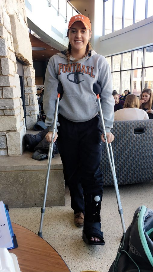 Kennedy McCullough shows off her new walking boot and crutches.
