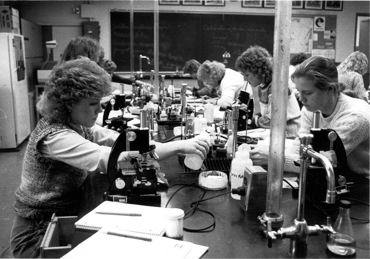 This 1980 photograph shows students in Biology class performing an experiment.
