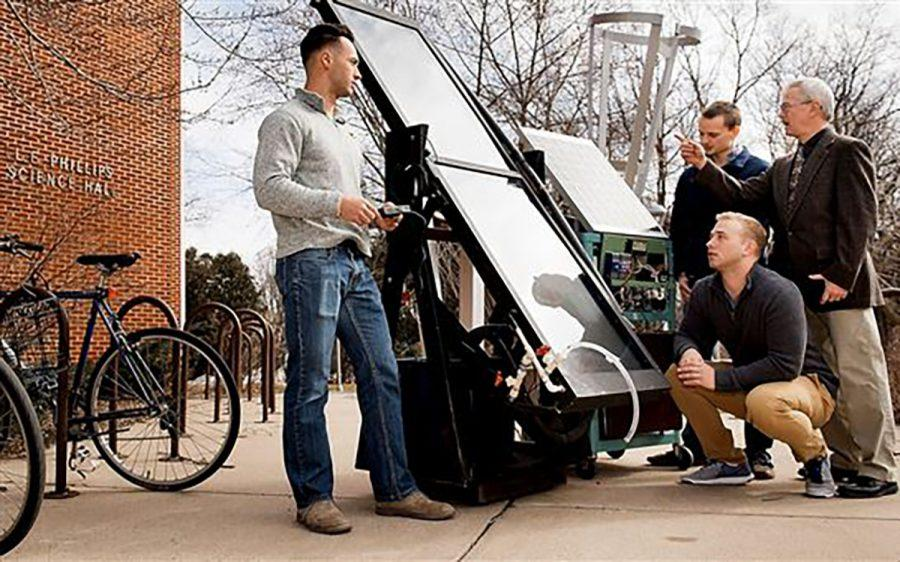From left, students Brendon Kwick, Sawyer Buck and Hunter Hermes, kneeling, and Professor Kim Pierson test their solar-powered water heater.