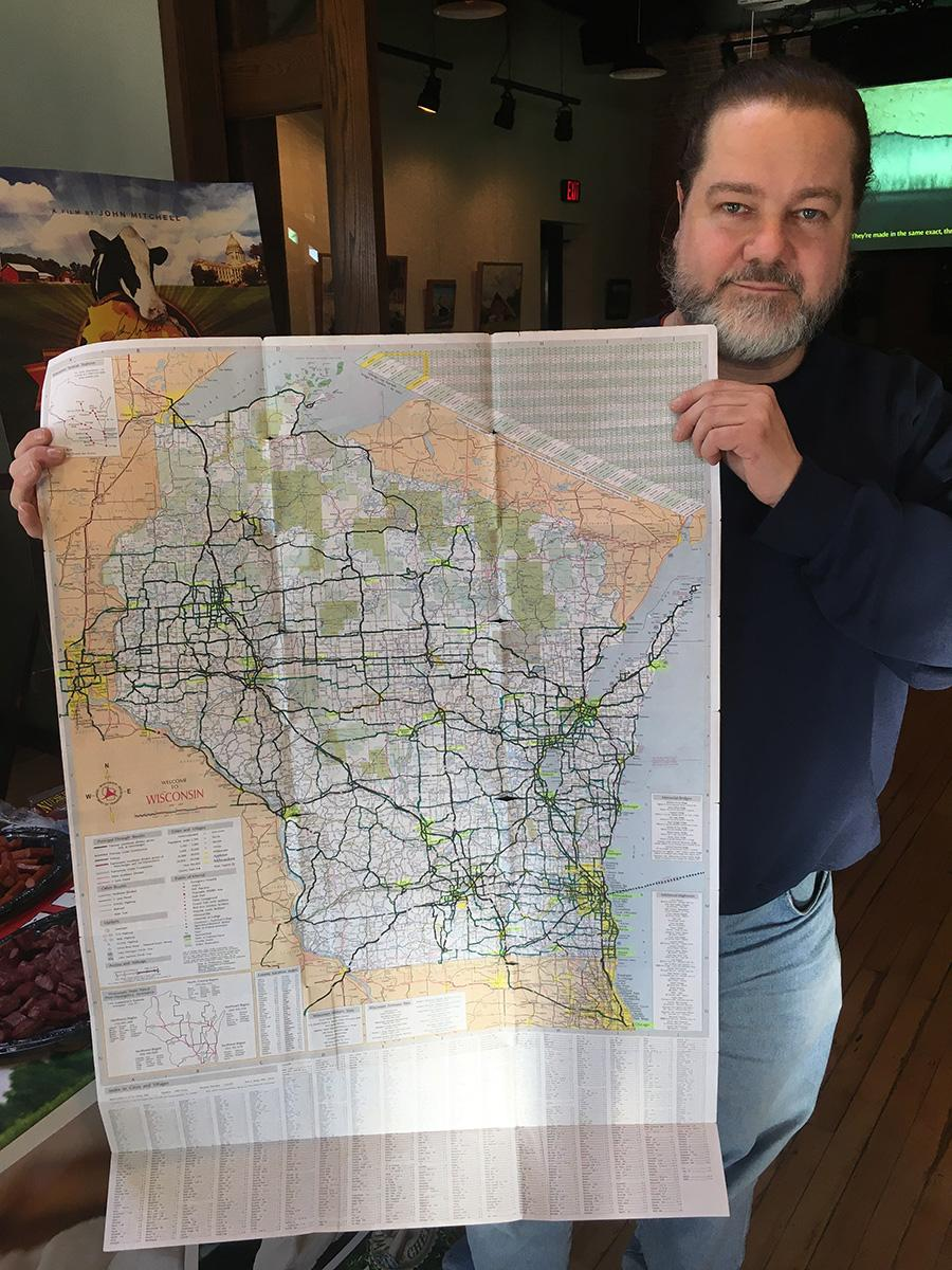 """John Mitchell holds a map tracing the roads he took and highlighting the towns he visited in the process of filming """"Cheeseheads,"""" a documentary about Wisconsin."""