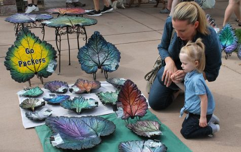 Mother and daughter glance over the art displays at the Eau Claire Farmers Market.