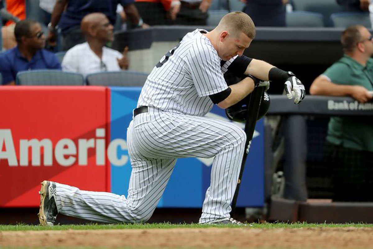 Yankees third baseman Todd Frazier kneels after young girl gets struck in face by foul ball.