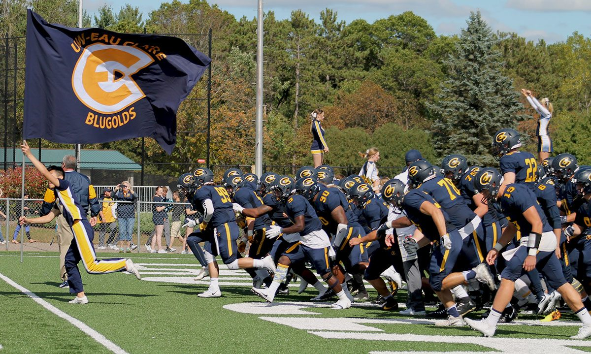 The UW-Eau Claire football team storms the field for the 2017 Homecoming game.