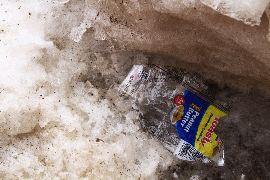 A plastic food wrapper drifts into a snow pile outside Hibbard Hall. The Pew Research Center reports that when it comes to total recycled items, plastics like bags and food packaging account for less than 20 percent.