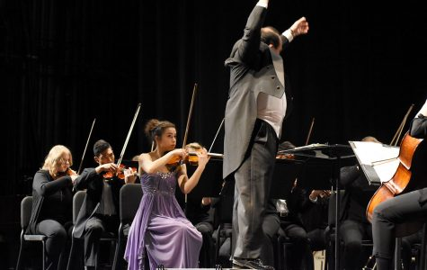 Winner of string division, Anne Schreiber, looks on to student conductor Carlos Rojo at Sunday's orchestra concert.