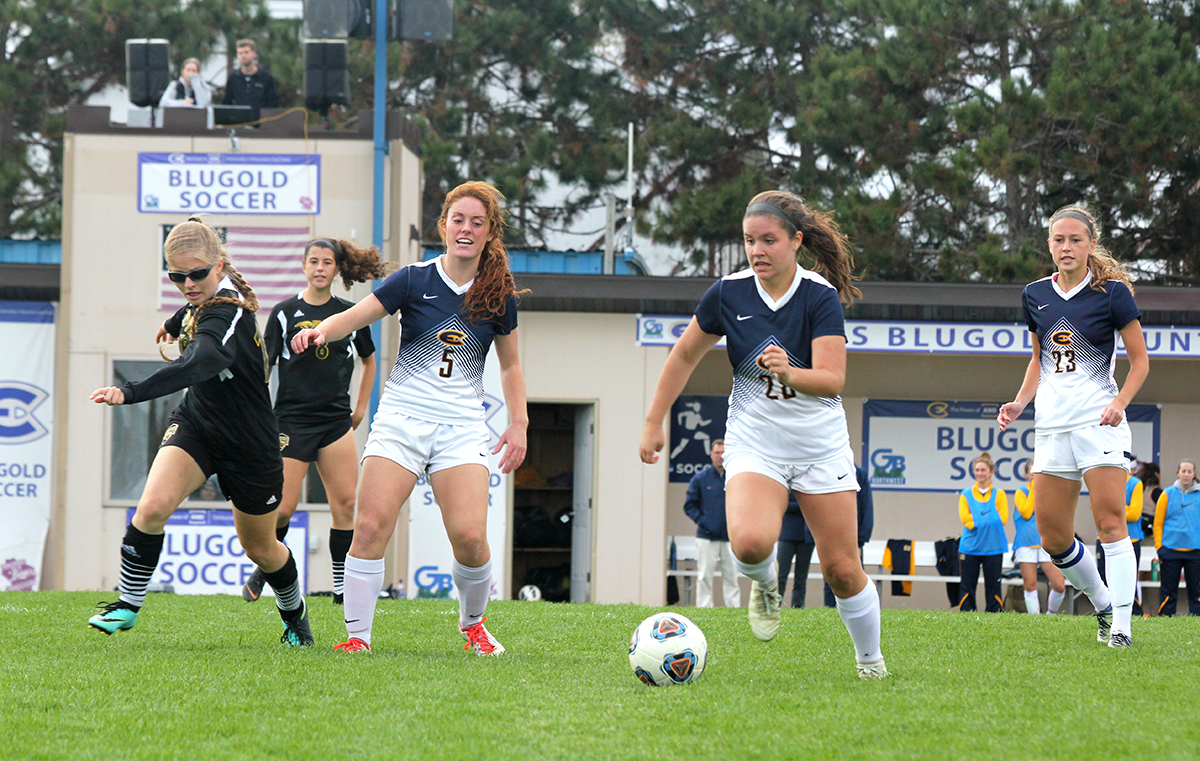 Emma Stange, a first-year midfielder, works with her teammate to drive the ball down the field.