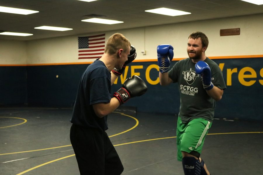 Levi Smith and Tanner Semb, members of the Mixed Martial Arts Club, practice their fighting moves on each other.