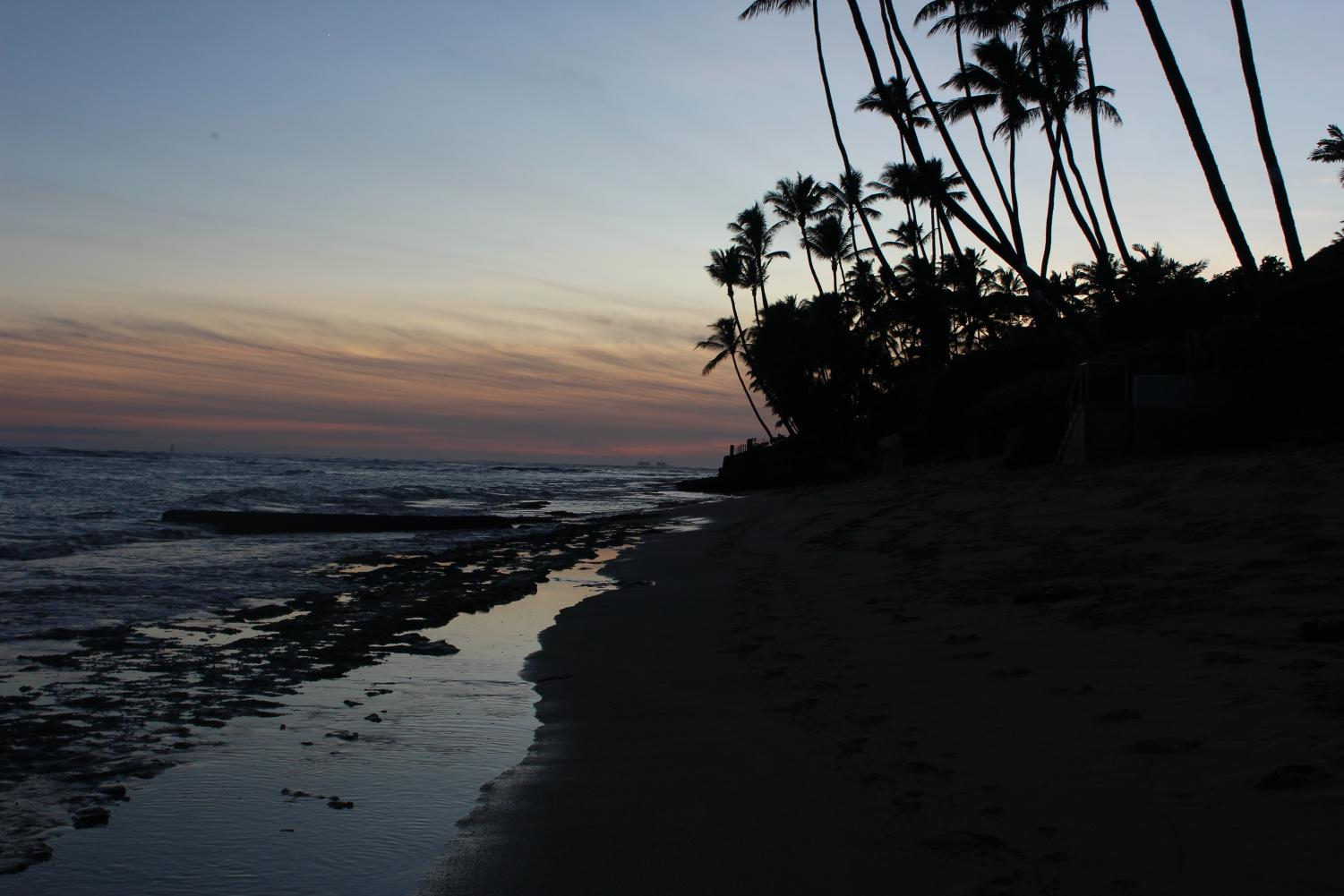 The sun sets and reflects into the ocean at a hidden beach close to campus called Cromwell's.