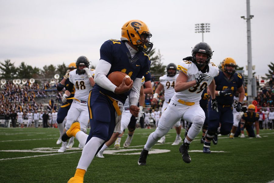 Scott Procter, a fourth-year quarterback, carries the ball as the Blugolds fly in for another win this season.