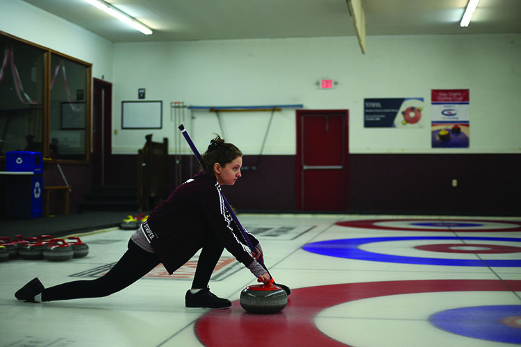 Andrea+Wendt%2C+a+fourth-year+student+at+UW-Eau+Claire%2C+demonstrates+how+to+throw+a+rock+in+curling.+%0A