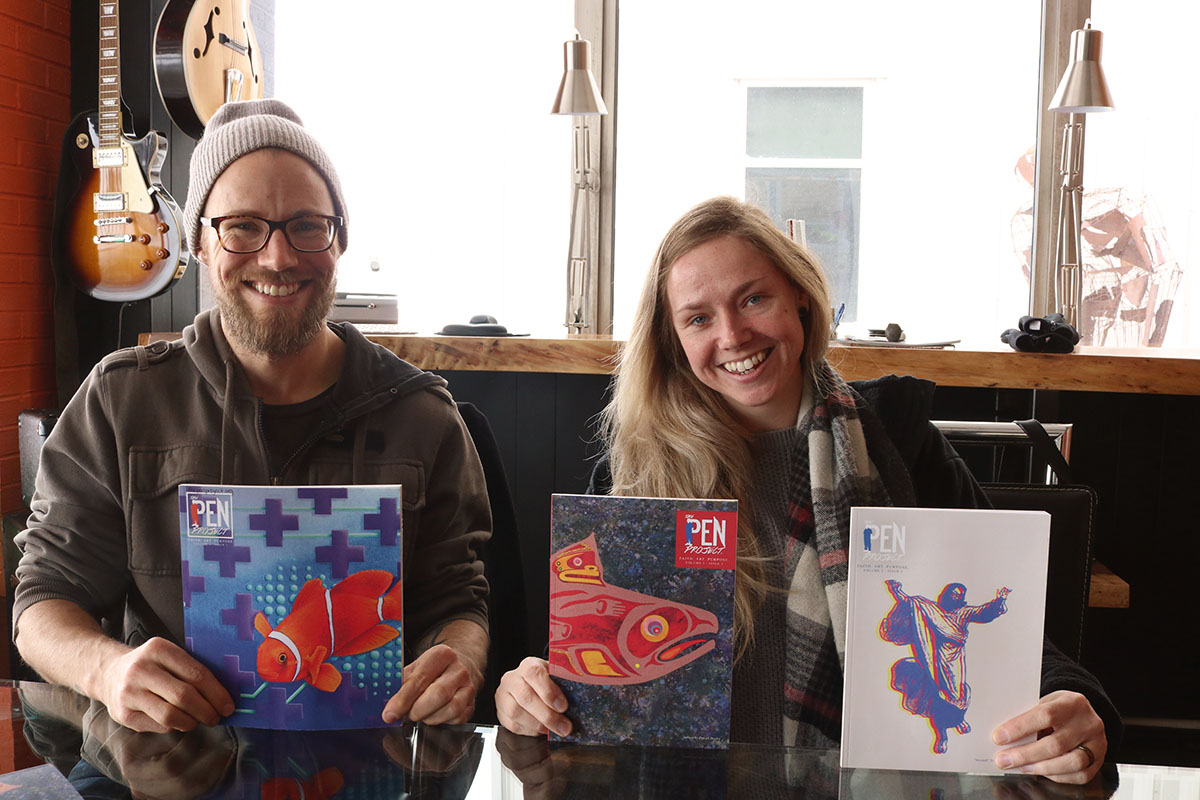 Artist Anthony Scholfield and The Pen Project director Keri White pose with three of the five printed issues of the art magazine.