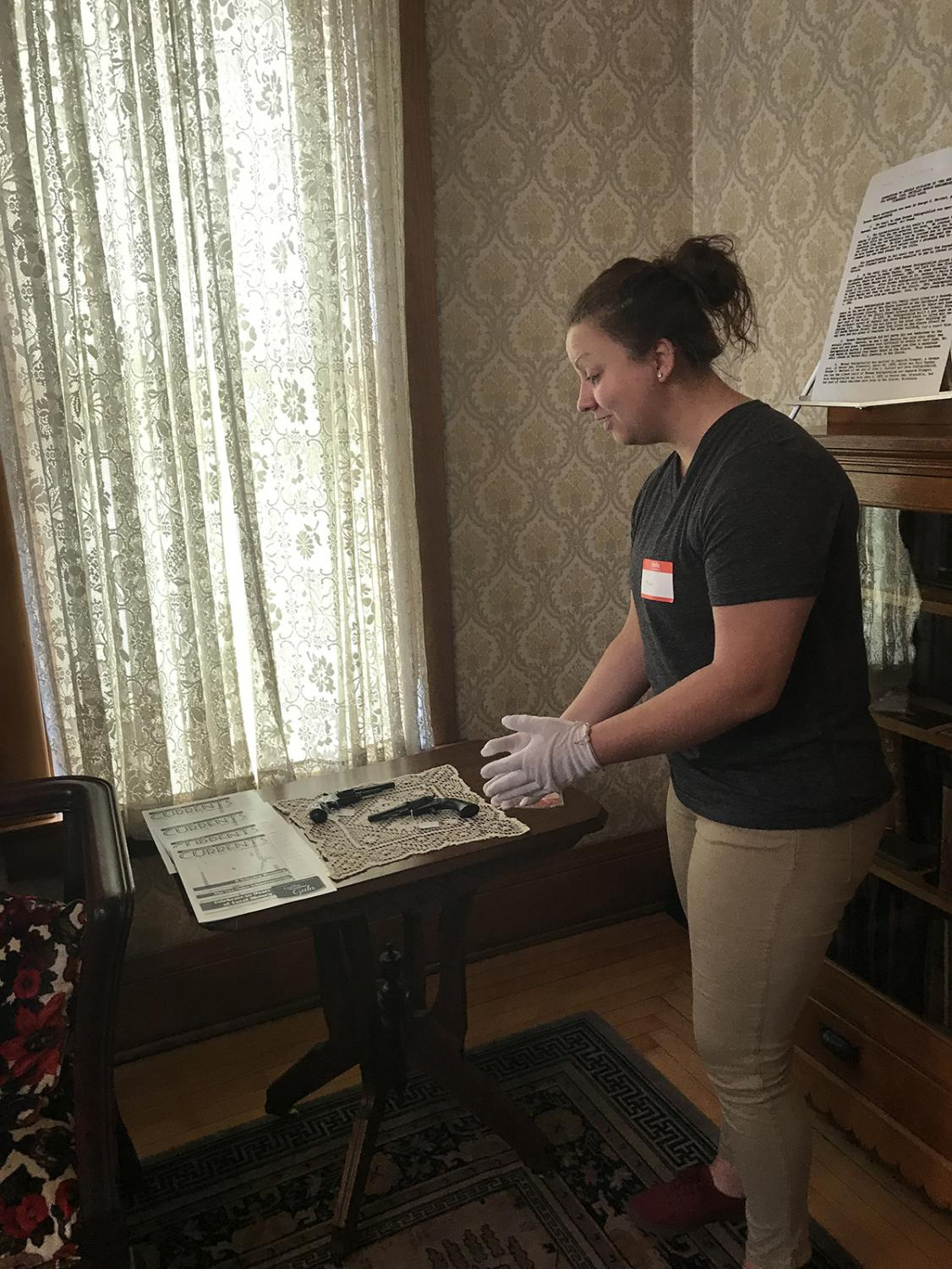 Madeline Jagodzinski, a student in John Mann's public history course, speaks about the Schlegelmilch guns during the tour inside the historic Schlegelmilch House.