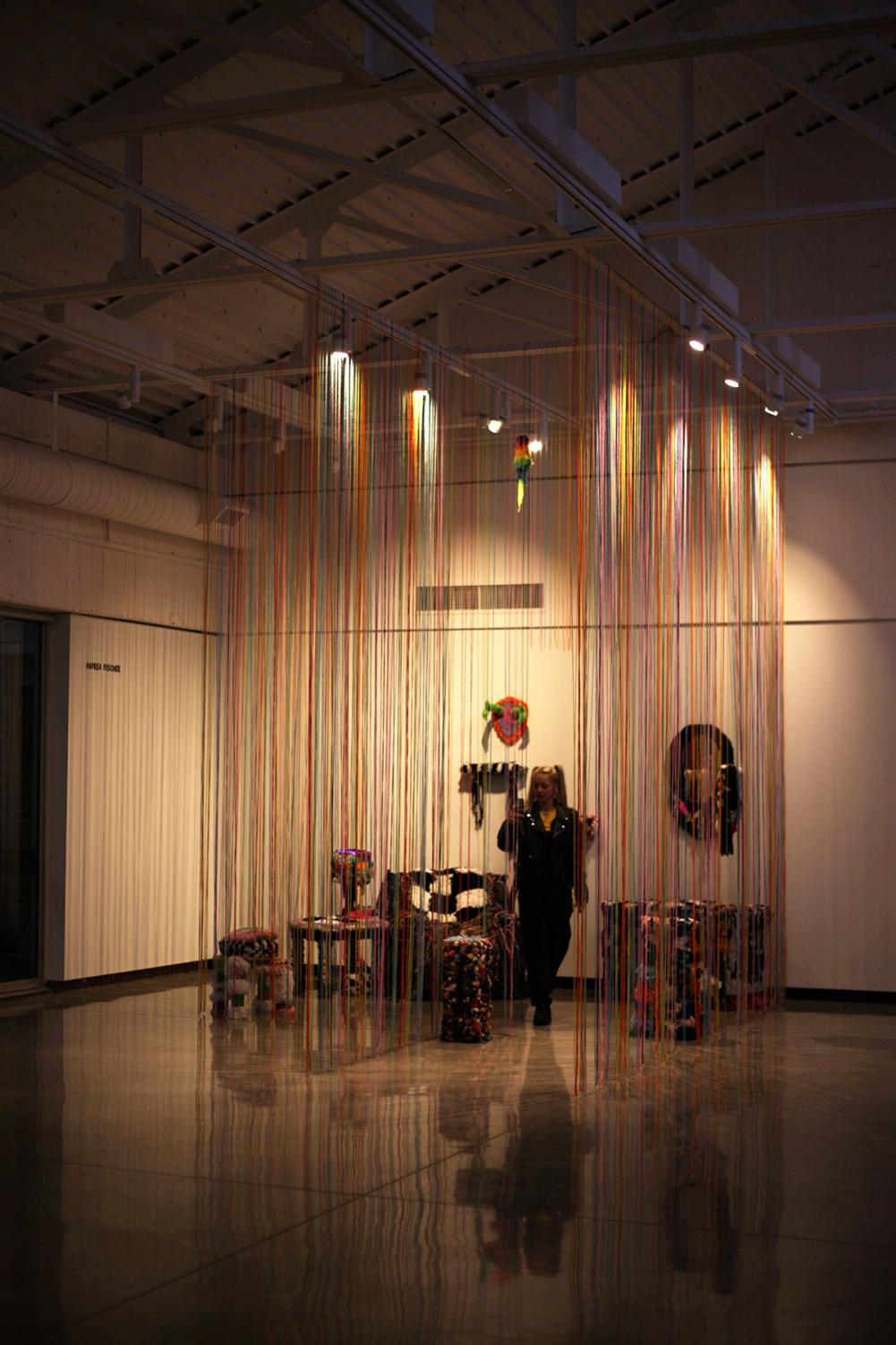 Andrea+Fischer%2C+a+fourth-year+photography+student%2C+stands+under+her+little+yarn+world+of+presented+work%2C+titled%2C+%E2%80%9Cfur-niture.%E2%80%9D